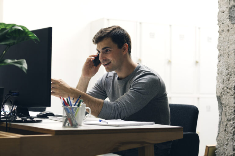 Cheerful businessman working in office. He has cheerful expression, pointing in monitor and talking on the phone.