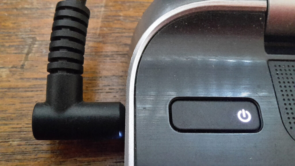 A close up picture of the power button to a laptop and its power cord